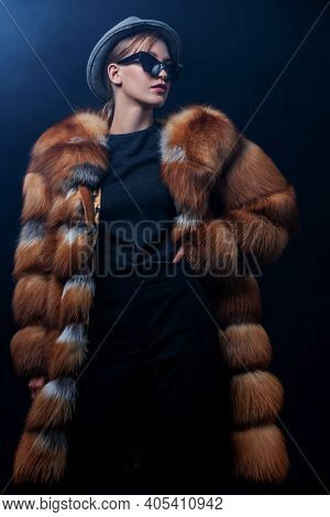 Fashion model posing in a luxurious fox fur coat on a dark blue background with snow. Winter fur coat fashion.