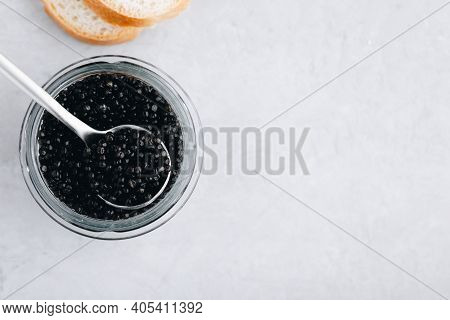 Black Caviar In Glass Jar With Spoon On White Stone Background, Luxurious Delicacy Appetizer. Top Vi