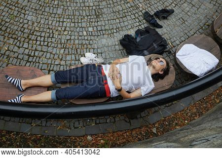 Man lying on a park bench having a nap on hot summer day