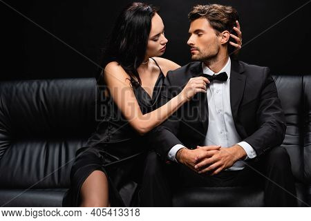 Seductive Woman Touching Bow Tie And Head Of Elegant Man While Seducing Him Isolated On Black.