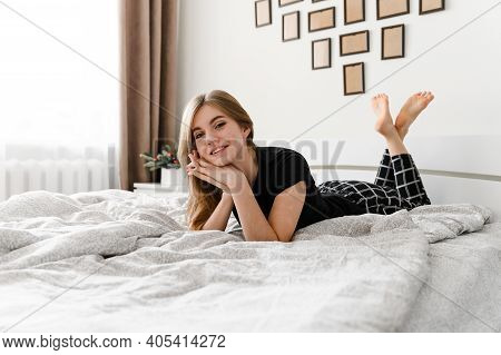 Sexy Young Girl Cheerfully Lies In Bed. A Girl With Her Head Down From The Bed. A Satisfied Girl Lyi