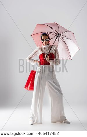Full Length Of Stylish Woman In Headscarf And Sunglasses Holding Red Umbrella And Shopping Bag While