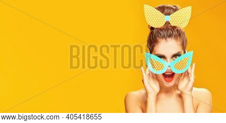 Pin-up style and beauty. Portrait of an exciting pretty woman posing in paper sunglasses and a bow in pin-up style on a yellow background. Makeup and cosmetics. Studio shot. Copy space.