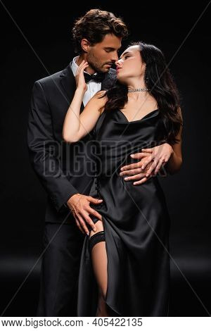 Man In Elegant Suit Hugging And Kissing Sexy Woman In Satin Dress On Black.