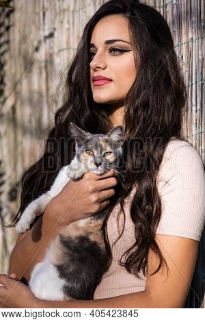 Beautiful Young Girl Holding A Calico Cat. Outdoors Photo