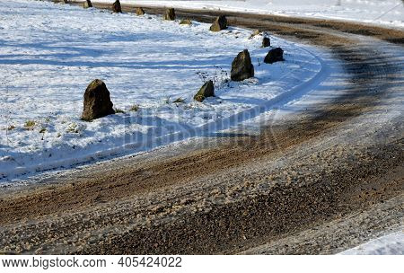 A Snowy Meadow And A Dirt Road With A Clattering Mud In A Bend. So That The Vehicles Orient Themselv