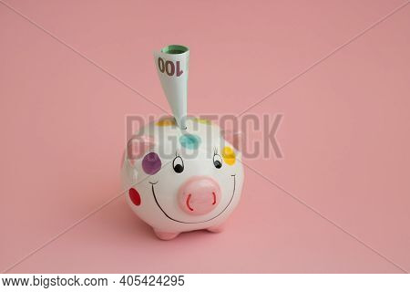 Piggy Bank In The Form Of A Pig On A Pink Background. A Rolled-up 100-euro Bill Sticks Out Of The Pi