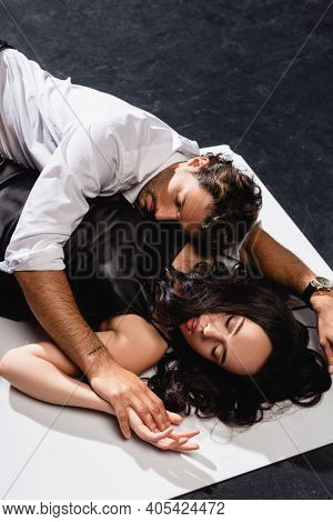 Overhead View Of Man In Shirt Seducing Woman In Satin Dress Lying On Black And White Floor.
