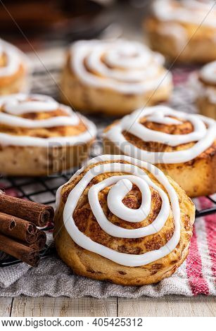 Baked Cinnamon Rolls With White Icing On A Cooling Rack
