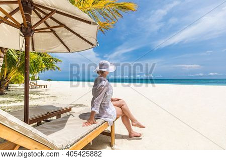Summer Beach Vacation Concept, Woman With Hat Relaxing On Chair At Calm Beach. Fashion Woman Relax O