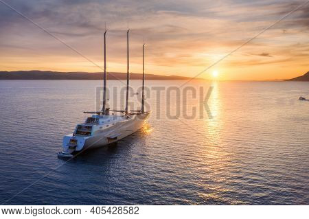 Aerial View Of Luxury Yacht In Blue Sea At Sunset In Summer. Big Modern Sail Boat. Top View Of Beaut