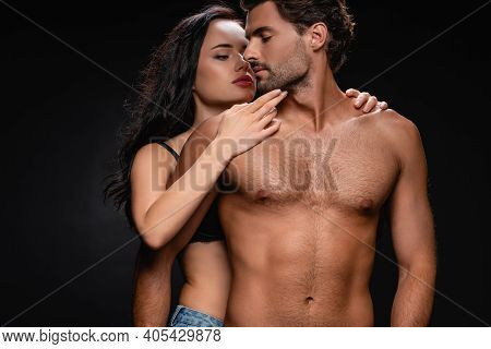 Sexy Brunette Woman Touching Chin Of Shirtless Man With Muscular Torso Isolated On Black.