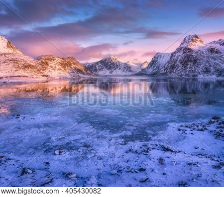 Aerial View Of Snowy Mountains, Blue Sea With Frosty Coast, Reflection In Water, Sky With Pink Cloud