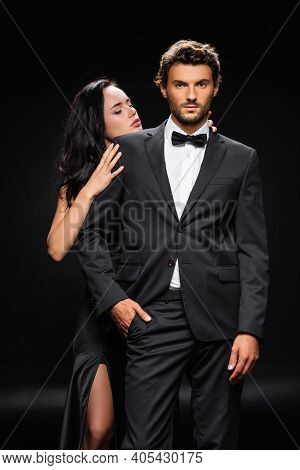 Passionate Brunette Woman Seducing Confident Man In Formal Wear On Black.
