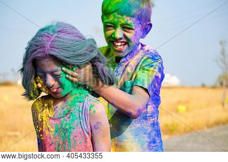 Young Kid From The Back Applying Holi Colors To Girls Face During Holi Festival Celebration - Concep