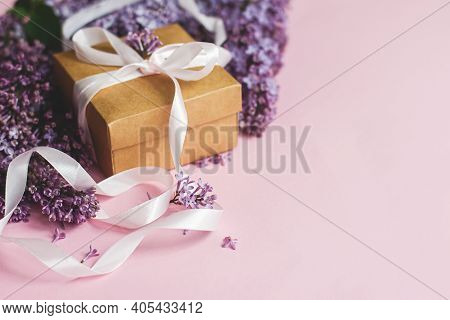 Happy Womens Day And Mother's Day Concept. Lilac Flowers And Gift Box On Pink Paper With Copy Space