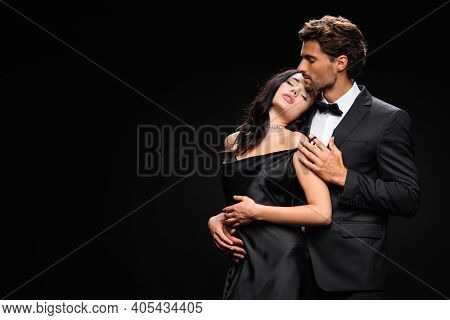 Young Man In Suit Hugging Passionate Woman In Satin Dress Isolated On Black.