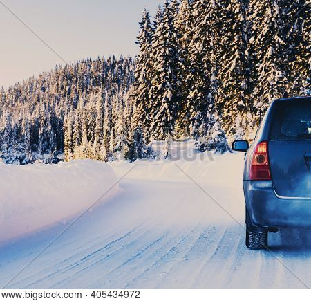 Car Driving On A Snow Covered Road In A Wilderness Forest On A Bright Sunny Winters Day.