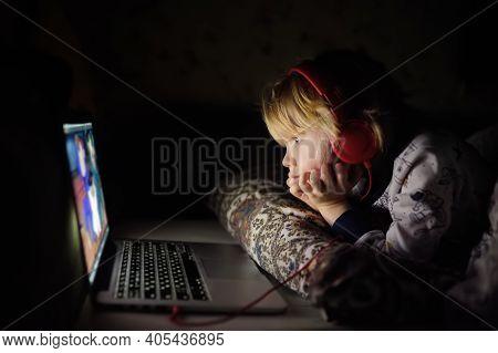 Cute Preschool Boy Wearing Headphones Is Watching Cartoon Movie By Laptop Before Sleeping In Bed Or