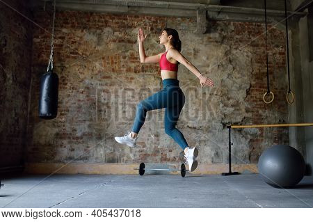 Sporty Woman During Hiit Workout. Dynamic Movement. Sportswoman Jumping High In The Process Of Train