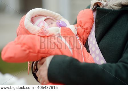 Newborn Baby Girl In Her Mother Arms. Baby Sleep Quietly And Sucks A Pacifier Warm Clothes For The B