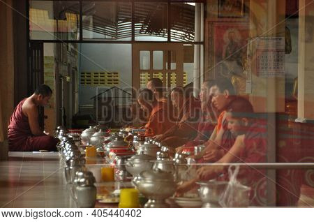 Nakhonsithammarat, Thailand - June 7, 2014: Group Of Monks At Table Durind. View Of Men In Red Robes