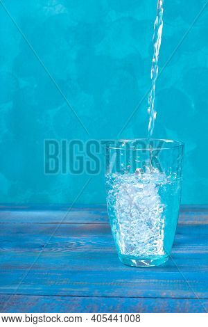 Purified Water Is Being Poured Into The Glass Against The Blue Background