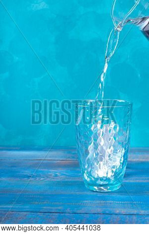 Purified Water Is Poured Into The Drinking Glass Out Of The Jug Against The Turquoise Background. Co