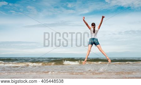 Happy Girl Jumping On The Beach At Day Time- Against Blue Cloudy Sky