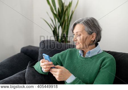 Senior Mature Woman Wearing A Green Jumper, Sitting On The Couch In The Living Room, Holding A Mobil