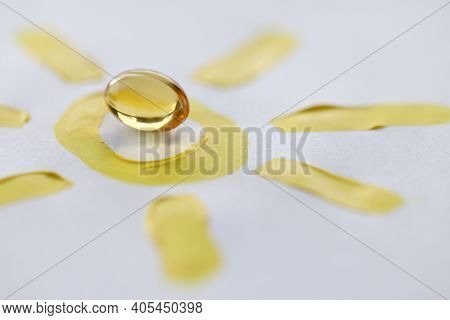 Yellow Transparent Vitamin D Pill Lying On Drawn Sun Closeup. Prevention Of Rickets Concept
