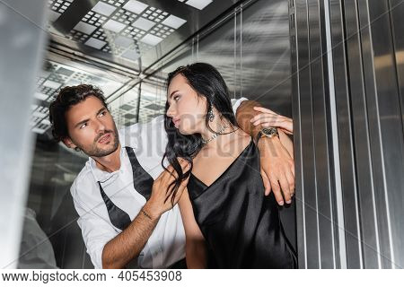 Passionate Man Seducing Sexy Woman In Black Satin Dress In Elevator, Blurred Foreground.