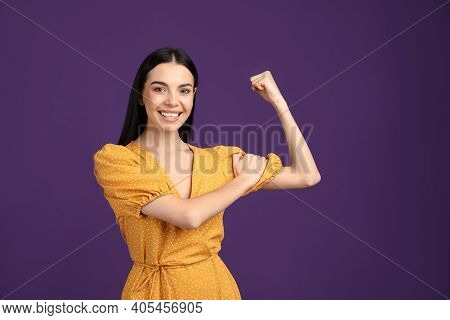 Strong Woman As Symbol Of Girl Power On Purple Background. 8 March Concept