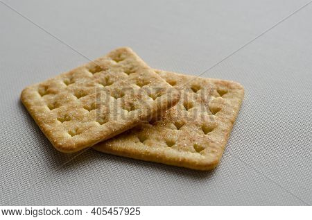 Square Salt Crackers On White Textured Background. Side View At An Angle Of Two Crispy Crackers. Foo