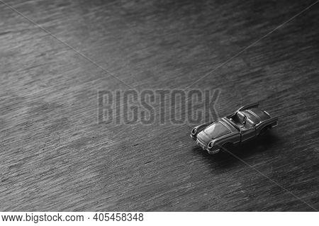 Children's Imaginary Concept Games. A Small Toy Car Rushes Along A Brown Wooden Surface. View From A