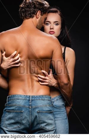 Passionate Woman Looking At Camera While Scratching Back Of Sexy Man Isolated On Black.