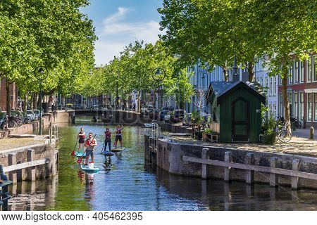 Gouda, Netherlands - May 21, 2020: Young People Paddling Through The Canals Of Gouda, Netherlands