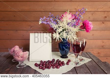 Empty White Frame, Beautiful Bouquet In Blue Vase, Glasses Of Red Wine, Fresh Cherry And  Glass Bowl
