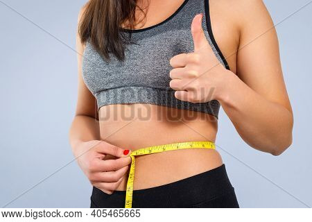 A Slender Woman Measures Her Waist With A Measuring Tape. Against A Yellow Background Close-up.