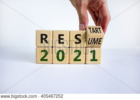 2021 Resume And Restart Symbol. Businessman Hand Turns Cubes And Changes The Word '2021 Resume' To '