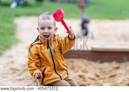 Toddler Sitting In Sandbox, Waving With Pink Toy Shovel - Enjoying Playground