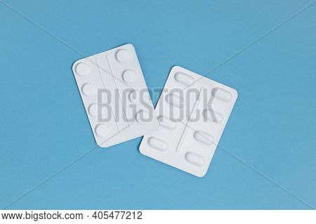 Two Blister Packs Of Tablets Isolated On A Bright Blue Background, Overhead View
