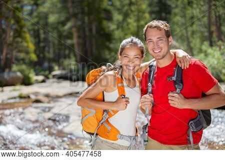 Happy hikers couple hiking in summer forest camping with backpacks. Two friends, Asian woman, Caucasian man smiling portrait, interracial group.