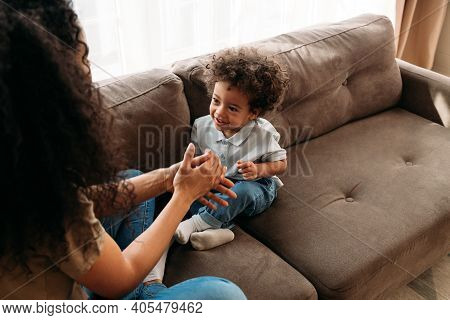 Little Boy Lying On Sofa And Laughing While Father Tickling Him