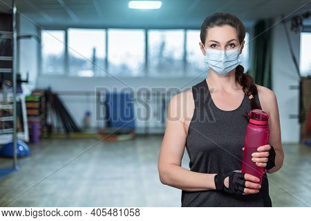 Woman Athlete In A Mask Stands With A Bottle Of Water On The Background Of The Gym.