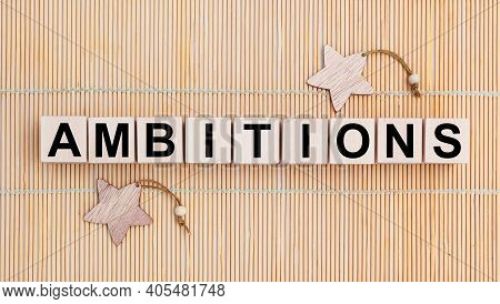 Wooden Cubes With The Abbreviation Ambitions On Wooden Background