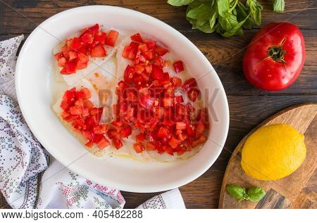 Raw Halibut Fish Fillet, Tomato, Lemon Basil And Spices. White Casserole On Wooden Rustic Table, Top