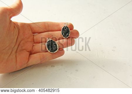 Two Pendants Made Of Natural Tektite Lie In The Palm Of A Woman's Hand. Handmade Jewelry Made From N