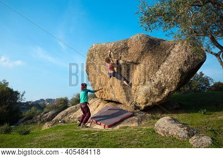 Two Young Girls Climb Bouldering Outdoors. Rock Climber Climbs A Difficult Route. Do Sports Outside