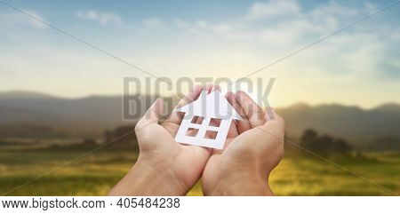 Hands holding paper house, family home and protecting insurance concept